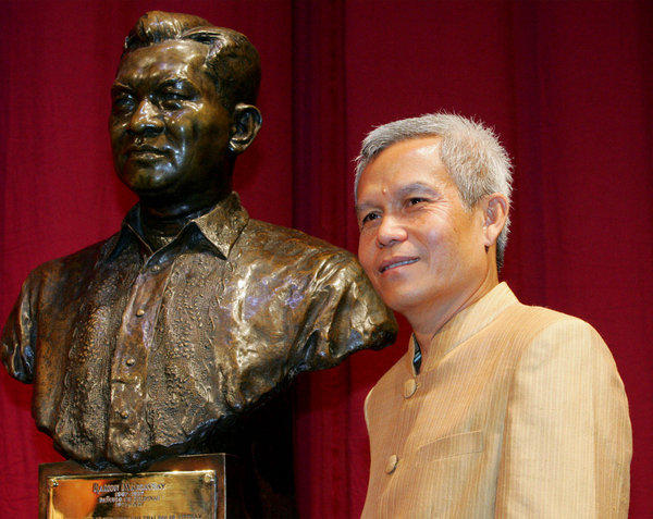 Laotian activist Sombath Somphone in 2005, posing with the bust of the late Philippine President Ramon Magsaysay before receiving the Ramon Magsaysay Award for Community Leadership at the Cultural Center of the Philippines in Manila.
