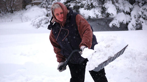 Lifetime Gaylord resident Jill Washburn muscles through a shovel load of heavy wet snow. As of Friday morning, the storm dumped 18 inches of snow on Gaylord.