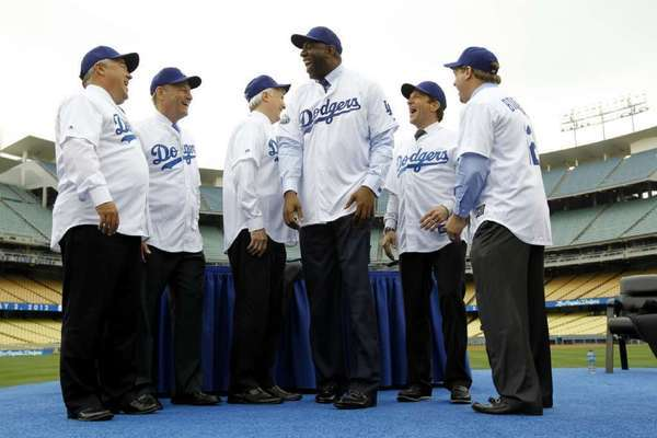 Members of the Guggenheim Baseball Management group, with Magic Johnson in the middle, pose for photos at the news conference introducing them as the new owners of the Dodgers.