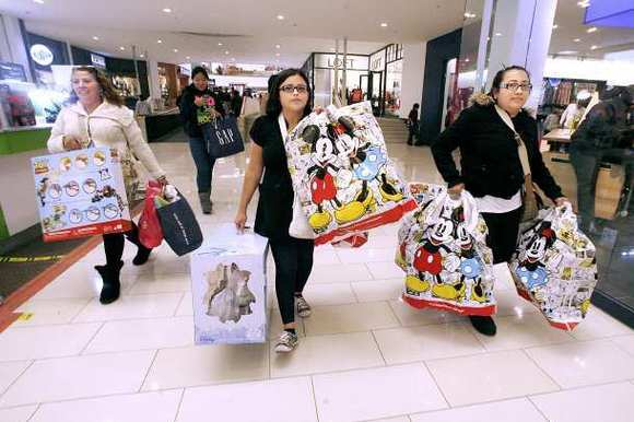 From left, Maria Quintero, of Glendale, Lisette Uribe of Glendale and Elsy Quintero of L.A., carry loads of bags from a shopping spree at the Glendale Galleria in Glendale on Black Friday, Nov. 23, 2012.