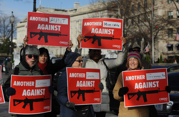 People protest the National Rifle Association of America news conference in front of the Willard Hotel, near the White House.