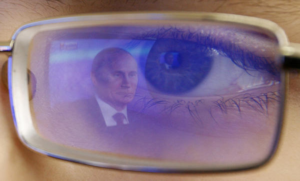 Russian President Vladimir Putin is reflected in the glasses of a cadet watching Putin's annual news conference on TV. Putin said on Thursday a U.S. law that punishes Russians who abuse human rights was poisoning ties with Washington but signalled support for a retaliatory ban on Americans adopting Russian children.