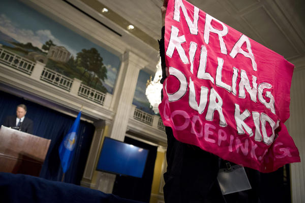 A protester holds up a sign during a speech by Wayne LaPierre (L), Executive Vice President of the National Rifle Association (NRA), during a news conference in Washington. NRA, the powerful U.S. gun rights lobby, went on the offensive on Friday arguing that schools should have armed guards, on a day that Americans remembered the victims of the Newtown, Connecticut school massacre