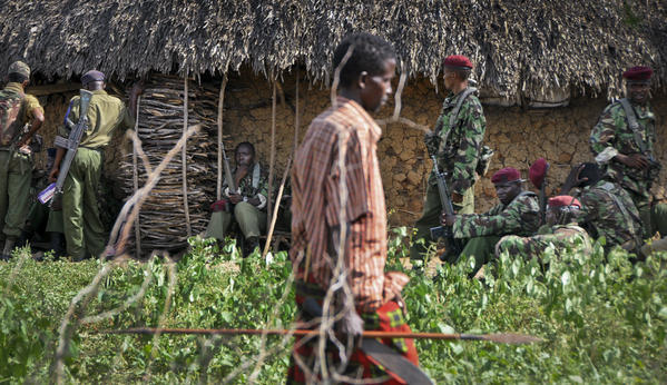 A villager armed with a spear walks past Kenyan police sent to keep order following tribal clashes in Kipao village on Friday.