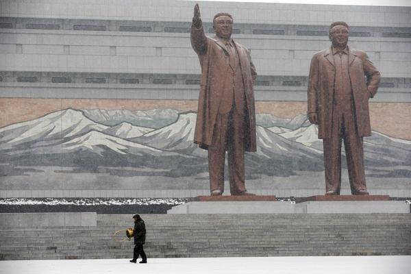 Statues of late North Korean leaders Kim Il Sung, left, and Kim Jong Il stand amid falling snow Friday at Mansu Hill in Pyongyang, North Korea.