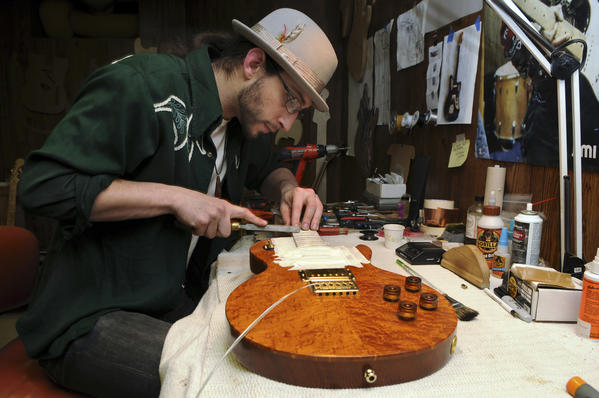 Stephen Balkun files the frets on the neck of a Les Paul style electric guitar he is making for a client in the workshop at his West Hartford home.  Balkun, a musician and luthier, is also a member of a band called Cashed Fools whose new CD will be released soon.