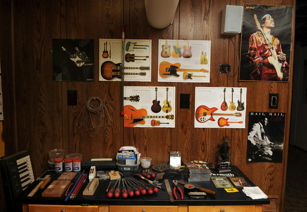 Tools of the luthier's trade lie neatly on a work bench beneath pictures of guitars and Jimi Hendrix in Stephen Balkun's workshop.