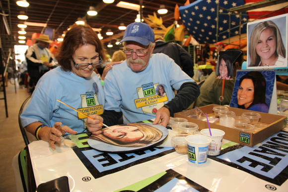 Dawn and Howard Mauer decorate a floragraph honoring their daughter, Fountain Valley High School alumna Deanna Maue, for the Donate Life Rose Parade float.
