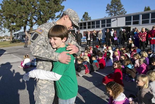 U.S. Army Spc. David Gustafson hugs his fourth-grade cousin, Thomas Marrs, who turned 10 years old on Friday, during a surprise visit at Harbor View Elementary School. Gustafson, who is stationed with the 10th Mountain Division out of Fort Drum, N.Y., and has been deployed to Afghanistan, came and wanted to surprise his little cousin.