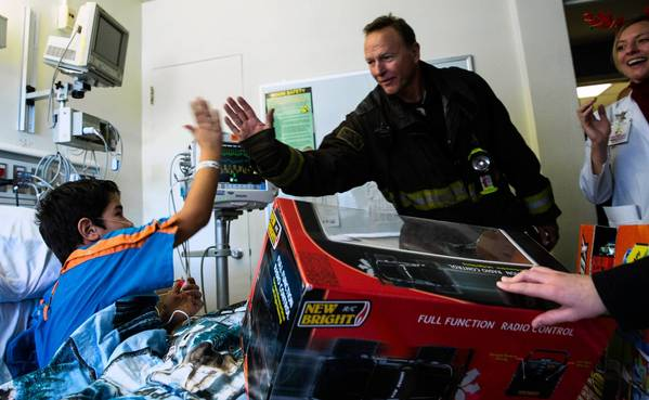 Nathan Maldonado, 7, high-fives Chicago firefighter Jim Kull on Friday after receiving gifts as part of a program in which local emergency responders deliver gifts to children at hospitals they typically visit during emergencies.