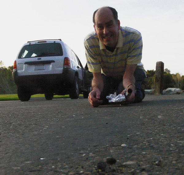 Peter Jenniskens, a meteor astronomer at NASA Ames Research Center and the SETI Institute in Mountain View, collects a sample of crushed meteorite using aluminum foil to avoid contaminating it.
