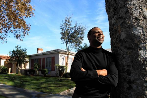 Tony Tolbert, of UCLA School of Law, is shown outside of the home he has been letting families live in rent free. He moved into a duplex with his mother to make it happen.