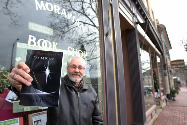 "Larry Deibert of Hellertown, author of a new fictional vampire book with a story based in downtown Bethlehem, poses in front of the Moravian Bookshop on Thursday afternoon. ""The Christmas City Vampire"" written by the retired Postal worker is Larry's second vampire story."