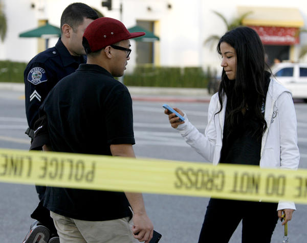 A Glendale policer evacuates two Starbucks employees, supervisor Vandyke Vicencio, left, and Talene Savadian, right, after a suspicious package was found at the Temple Sinai of Glendale on the 1200 block of N. Pacific Ave. in Glendale on Friday, December 21, 2012.