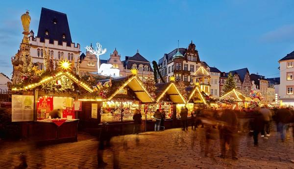 Visitors walk past illuminated stands of a Christmas market at the Hauptmarkt in Trier, western Germany.