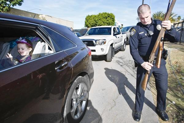 "A youngster waits in the back seat of a car as Blake Williams of the San Diego Police Department carries two rifles turned in by the driver at the city's annual ""Guns-for-Gift-Cards."" Hundreds of participants received gift cards worth $50 for rifles and $100 for handguns."