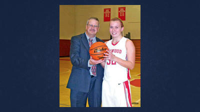 Rockwood's Sam Emert is presented the game ball by Rockwood coach John Oleskey in recognition of her 500th career rebound.