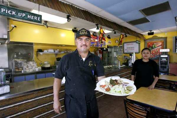 Leonardo Sandoval from Victoria's Tacos & Grill holds the fish taco, with Beatriz Lopez in the background, on the 4200 block of San Fernando Road in Glendale.