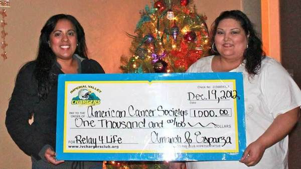 Imperial Valley Chargers Fan Club president Amanda Jo Esparza (left) presents American Cancer Society Relay 4 Life Krewe of Hope team captain Melissa Rodriguez with a check for $1,000 Wednesday in El Centro.