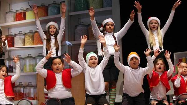 'Elves' raise their hands in desperation for having too many candy canes to make during a musical performance Tuesday at McCabe Elementary School in El Centro.