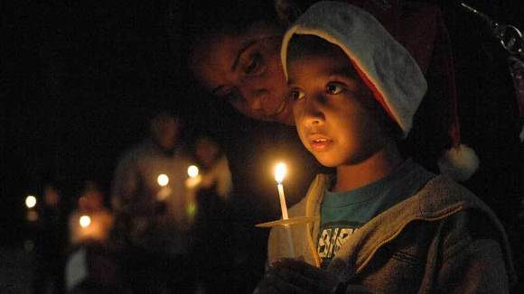 Maria Herrera (left) whispers to her son Julio Castillo, 7, during a candlelight vigil.