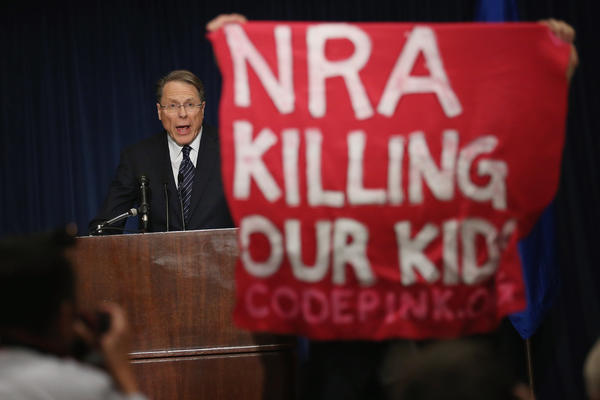 A demonstrator from CodePink holds up a banner as National Rifle Association Executive Vice President Wayne LaPierre delivers a statement.