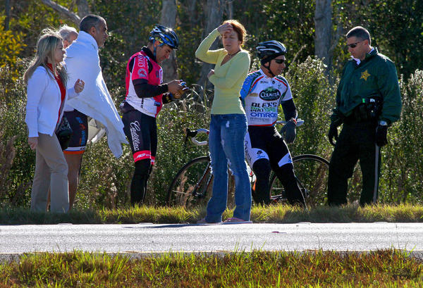 Bicyclists and bystanders talk with police on U.S. 27 just north of Griffin Road.  Four bicyclists were struck and injured by a car on U.S. 27 in Weston Saturday, according to the Broward Sheriff's Office