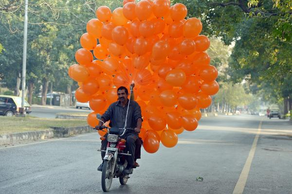 A Pakistani vendor rides his motorcycle as he delivers balloons in Islamabad on December 22, 2012. Year-on-year inflation stood at 6.9 percent in November, the State Bank of Pakistan said in a statement, a faster fall than had been estimated. Food inflation dropped to 5.3 percent and non-food inflation to 8.1 percent.