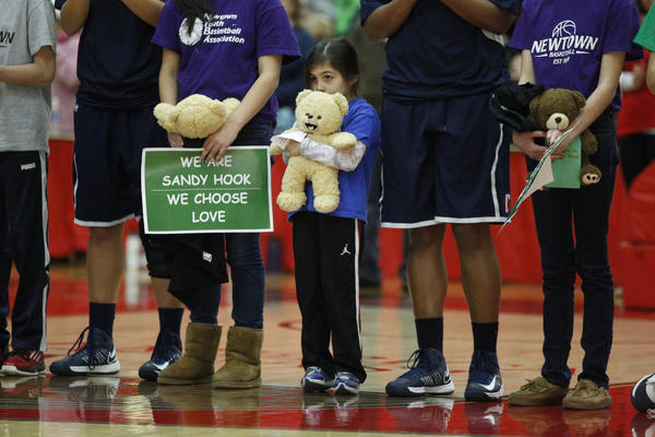Before the start of the game at the Chase Family Arena, children from the Newtown youth basketball league join the Connecticut Huskies and the Hartford Hawks to remember those killed Dec. 14 at the Sandy Hook Elementary School.