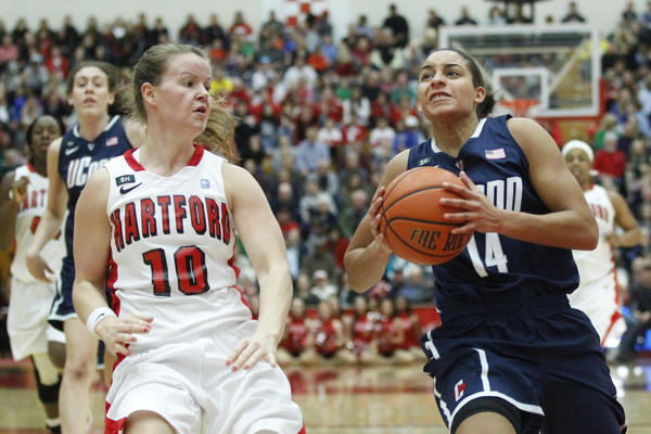 Connecticut Huskies guard Bria Hartley drives against Hartford Hawks guard Alex Hall during the first half at the Chase Family Arena.