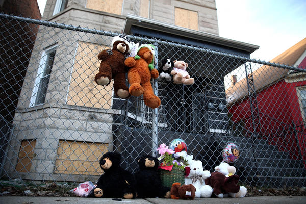 A memorial of stuffed animals marks the house where two children died in a fire.