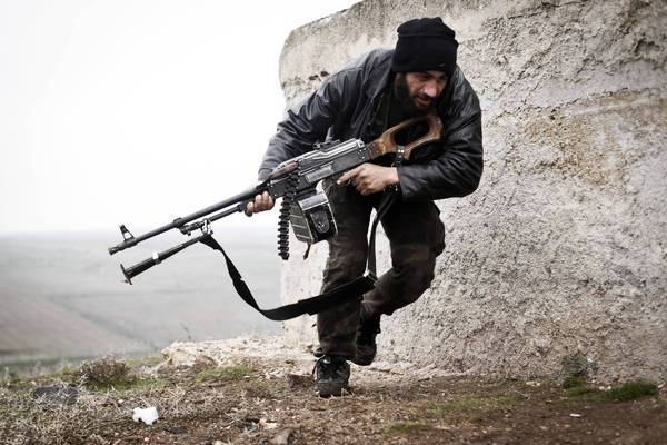 A Syrian opposition fighter takes cover during fighting in Azaz.
