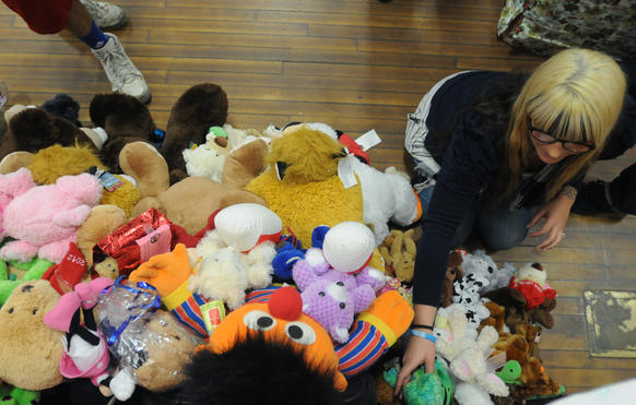 Volunteer Jenni Maddalena of Blue Point, N.Y., puts stuffed animals out for distribution to children in Edmond Town Hall in Newtown Saturday.