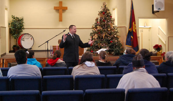 Lt. Jason Burns leads a chapel service Friday at The Salvation Army for families who received Angel Tree gifts this year.