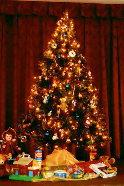 This Christmas tree at the Women's Club is decorated with teddy bears, Santas, candy canes and other items. There are many older toys under the tree, including an antique doll, keyboard, Lincoln Logs, Tinker Toys and games.