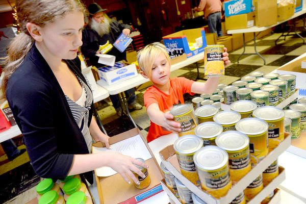 Amber Ahalt,14, left, of Hagerstown and Dalton Showe, 8 of Hagerstown pick cans of food to pack in to boxes for needy families Saturday afternoon at the Williamsport Moose Lodge #2462. The 5th annual Christmas Families program will help feed 25 families in the Williamsport area.