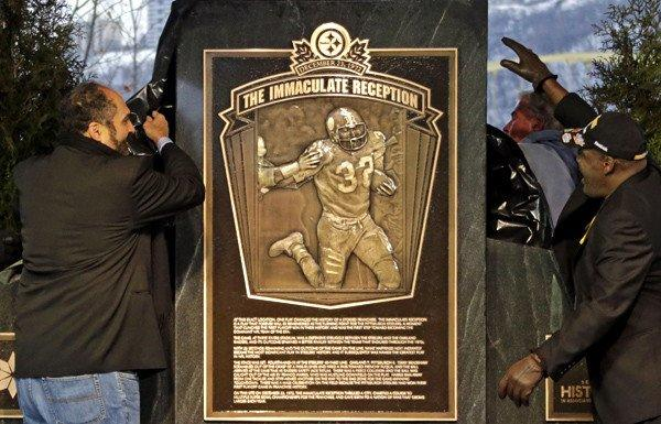 Franco Harris, left, and Frenchy Fuqua unveil a monument commemorating the Immaculate Reception, which took place on Dec. 23, 1972, during a playoff win over the Oakland Raiders.