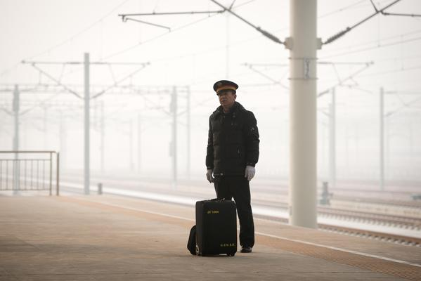 A train driver stands at a high-speed rail platform in Hebei province near Beijing on December 22, 2012. China showed off the final link of the world's longest high-speed rail route, set to open on December 26, stretching from Beijing to the southern Chinese city of Guangzhou. Travelling at around 300 kph, trains on the new route are expected to cover the 2,298-kilometre (1,425-mile) journey in a third of the current time from 22 hours to eight.