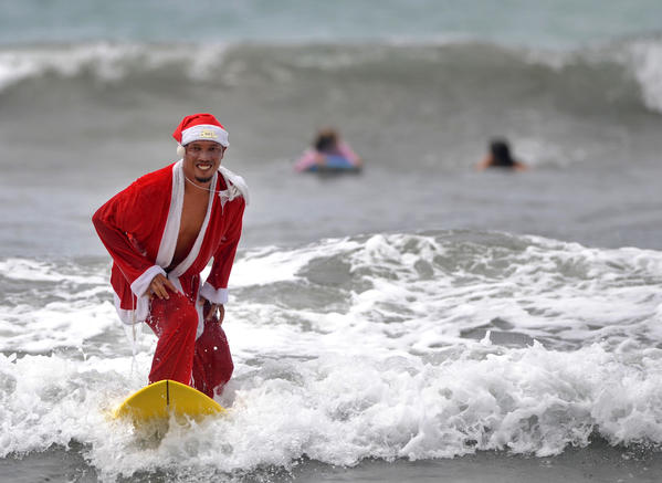 A Balinese surfer dressed in a Santa Claus outfit surfs at Kuta beach near Denpasar on Indonesia's resort island of Bali on December 22, 2012. The popular resort island, a pocket of Hindu culture in a country with the biggest Muslim population in the world, receives thousands of tourists every year over the Christmas season.