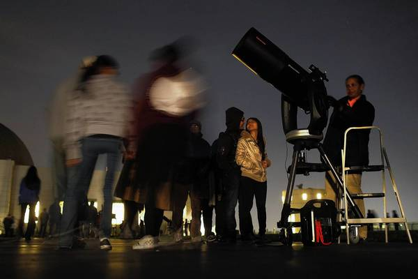 Mary Brown uses a telescope to observe the sky from the grounds of the Griffith Observatory during the winter solstice, the shortest day of the year.