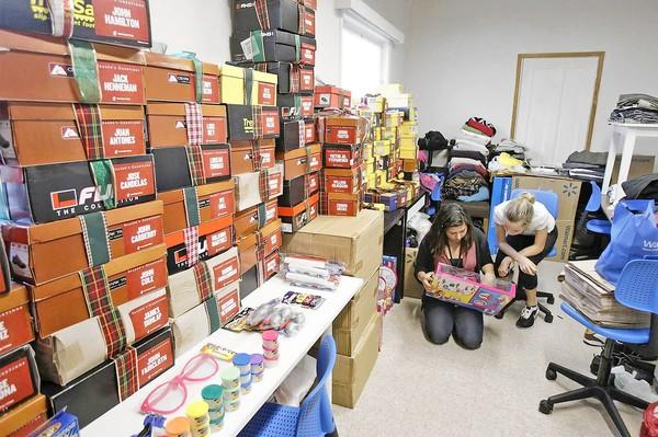 Volunteers Sam Imada, left, of Huntington Beach, and Kallie Foster, of Westminster, look at items in a storage room before helping hand out shoes to homeless people at Lighthouse Christian Church in Costa Mesa on Saturday.