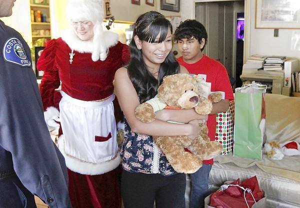 Emily Mite, 15, clutches her brand new teddy bear as she admires gift bags delivered by the Costa Mesa Fire Department on Saturday.