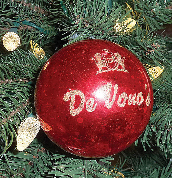 "The ornament reads De Vono's, the name of a past fine men's store in Hagerstown at Long Meadow.  My now husband and I had been dating for three months that Christmas of 1969. He was a very handsome and very nicely dressed man. Before the ""age of electronics,"" buying gifts for a man was not an easy thing. I thought a gift certificate for some more nice clothing would be perfect.  His gift certificate came rolled up and stuck into this bright, red shiny ball.  This was the start of a tradition of collecting one special ornament each year.  When this extensive collection was retired in favor of our granddaughter's ornament collection, the De Vono's ball was placed with hers and still holds the place of honor for longevity at the top of the tree.  It has remained treasured and displayed on the Wilson tree for 43 seasons.  ¿ By Bonnie and Paul Wilson,   Martinsburg, W.Va."