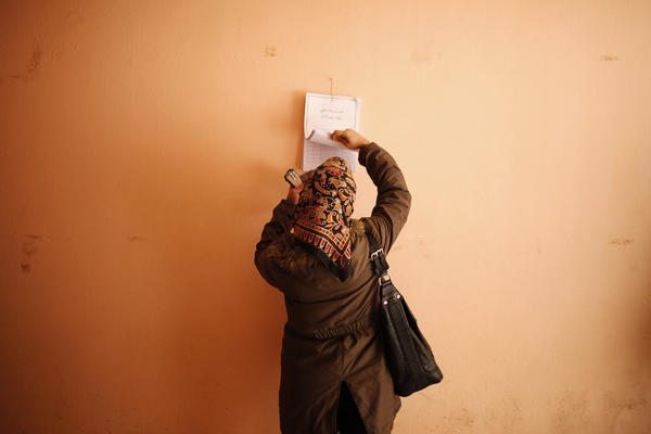 A woman looks for her name at a polling station before voting during the second and final round of a referendum on Egypt's new constitution, in Giza.