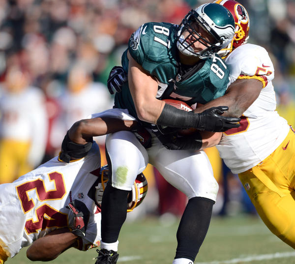 Philadelphia Eagles tight end Brent Celek (87) is tackled by Washington Redskins strong safety DeJon Gomes (24) and Washington Redskins linebacker Roddrick Muckelroy (55)  at Lincoln Financial Field in Philadelphia on Sunday.
