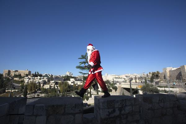 A Palestinian man dressed up as Santa Claus carries a Christmas tree and rings a bell as he walks along the wall of Jerusalem's Old City, on December 23 2012, as Christians around the world prepare for Christmas celebrations.