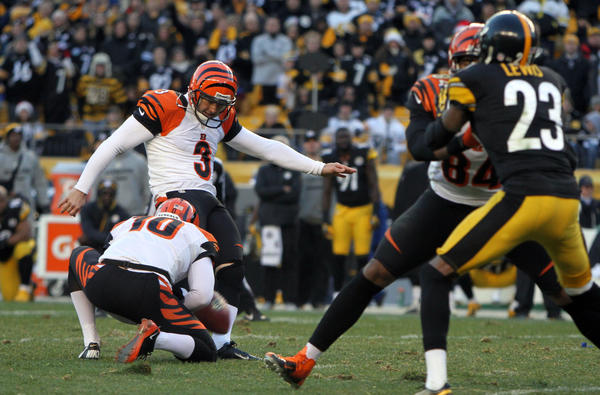 Cincinnati Bengals kicker Josh Brown (3) kicks a game-winning field goal against the Pittsburgh Steelers as holder Kevin Huber (10) holds the snap during the second half of the game at Heinz Field. The Bengals won the game, 13-10.