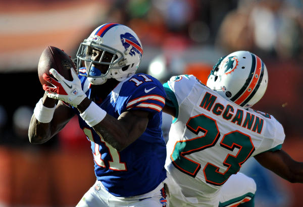 Buffalo Bills wide receiver T.J. Graham (11) hauls in a catch as Miami Dolphins defensive back Bryan McCann (23) defends the play during the second half at Sun Life Stadium. Mandatory Credit: