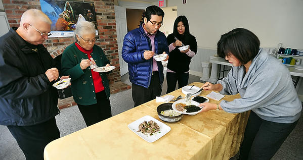 Hagerstown Korean Church members sample a traditional holiday meal Tuesday. Soyoung Lehtimaki, foreground, prepared thucok, or rice cake soup, with other dishes of beef, noodles and vegetables, and seaweed. From left, Harold Pereschuk, Hyo Chong Pereschuk, pastor Yo Han Chin, Un Hee Thacker, and Soyoung Lehtimaki.