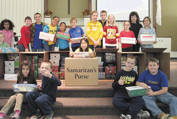 Elementary chapel students and chapel leader, Michelle Snodderly, gather around the shoe boxes that were collected for the Operation Christmas Child project. Front row, from left, Indira Aranha, Elijah Hawkins, Lily Kim, Trevor Ott and Riley Wallman. Back row, Serena Stevens, Alyssa Pinto, Jacob Gibson, Nathaniel Drier, Kahrisa Mann, Alani White, Grace Thornsbury, Katie Timmons, Timothy DeLloyd, Cassandra Derby, Sloane Walters, Snodderly and Lauryn Alexander.
